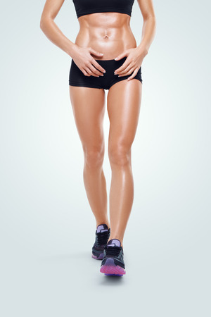 WOMAN FITNESS: Fitness sporty woman on a sportswear walking after workout. Closeup image of the strong legs and abs showing Stock Photo