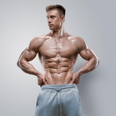 Knappe macht athletic jonge man met een grote lichaamsbouw. Sterke bodybuilder met zes pack abs perfecte schouders biceps triceps en borst. Studio-opname op een witte achtergrond