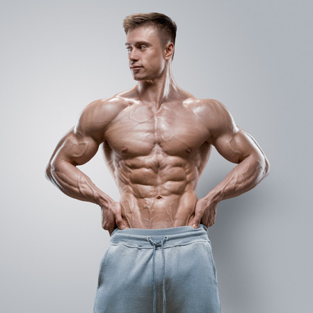 Handsome power athletic young man with great physique. Strong bodybuilder with six pack perfect abs shoulders biceps triceps and chest. Studio shot on white background