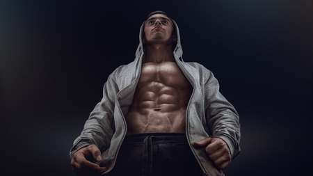 Bottom view of young strong bodybuilder showing off his physique against black background. Confident young fitness man with strong hands abs and abdominal muscles. Dramatic light.