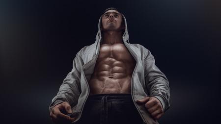 abdominal fitness: Vista inferior del joven culturista fuerte muestra apagado su constitución contra el fondo negro. Hombre confidente joven de la aptitud con las manos fuertes abdominales y los músculos abdominales. Luz dramática.