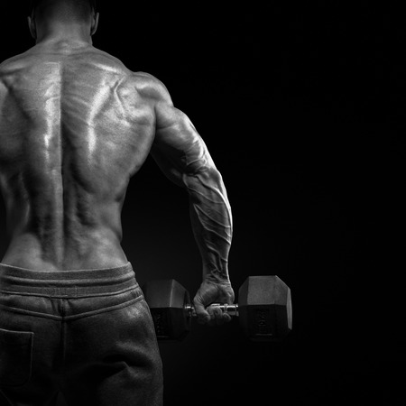 male bodybuilder: Muscular male model bodybuilder doing exercises with dumbbells turned back. Isolated over black background. Stock Photo
