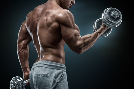Handsome power athletic man in training pumping up muscles with dumbbells. Strong bodybuilder with six pack perfect abs shoulders biceps triceps and chest.