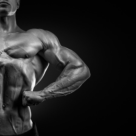 latissimus: Handsome muscular bodybuilder posing on Front Lat Spread display lat width from the front chest thickness shoulder width front arm and forearm size quadriceps mass and separation and calf development from the front