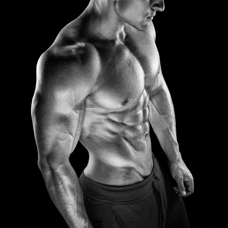 Young athletic man torso showing six pack abs. Strong bodybuilder with six pack perfect abs shoulders biceps triceps and chest Stock Photo