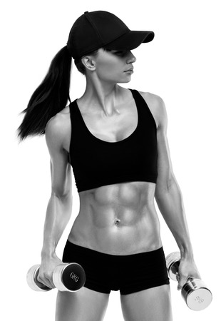 Fitness sporty woman in training pumping up muscles with dumbbells isolated on white background. Strong abs showing. Black and white image with copyspace for text. Standard-Bild