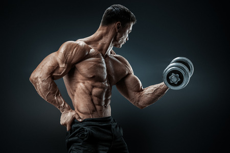 hard: Handsome power athletic man in training pumping up muscles with dumbbell. Strong bodybuilder with six pack perfect abs shoulders biceps triceps and chest Stock Photo