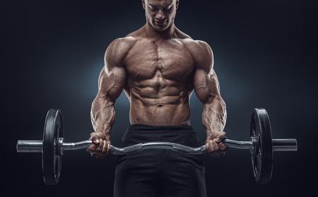 ジムでバーベルで筋肉男試しのポートレート、クローズ アップ。完璧なシックス パックの abs を持つ残忍なボディービルダー アスレチック男肩上腕