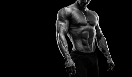 pectoral: Muscular and fit young bodybuilder fitness male model posing over black background. Black and white photo with copy space