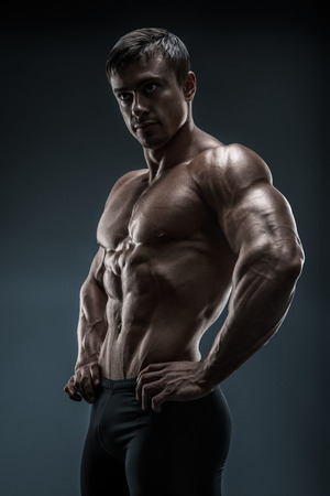 body building: Muscular and fit young bodybuilder fitness male model posing over black background. Studio shot on black background.