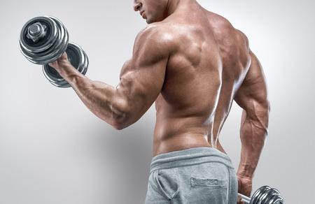 Knappe macht athletic man in training oppompen spieren met halter. Sterke bodybuilder met zes pack perfecte abs schouders biceps triceps en borst. Afbeelding met het knippen van weg