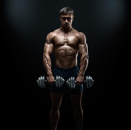 bodybuilder: Poder guapo chico atlético culturista haciendo ejercicios con mancuernas. Musculoso cuerpo fitness en el fondo oscuro.