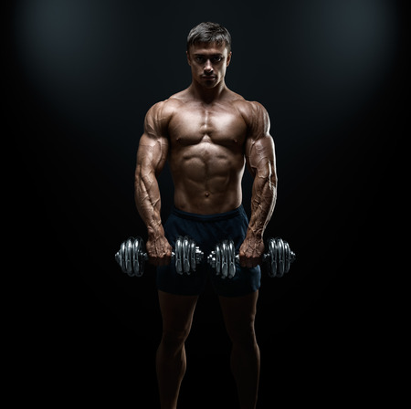 Handsome power athletic guy bodybuilder doing exercises with dumbbell. Fitness muscular body on dark background. Banque d'images