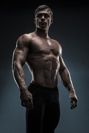hombre deportista: Culturista muscular hermoso prepara para el entrenamiento de fitness. Estudio disparó sobre fondo negro.