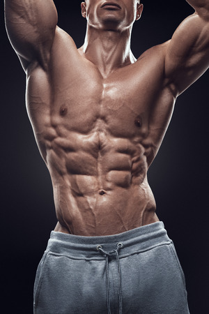 hands on stomach: Handsome power athletic young man with great physique. Strong bodybuilder with six pack perfect abs shoulders biceps triceps and chest. Image have clipping path