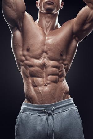 Knappe macht athletic jonge man met een grote lichaamsbouw. Sterke bodybuilder met zes pack abs perfecte schouders biceps triceps en borst. Afbeelding hebben het knippen weg