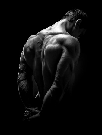 Handsome muscular male model bodybuilder preparing for fitness training turned back. Studio shot on black background. Black and white photo.