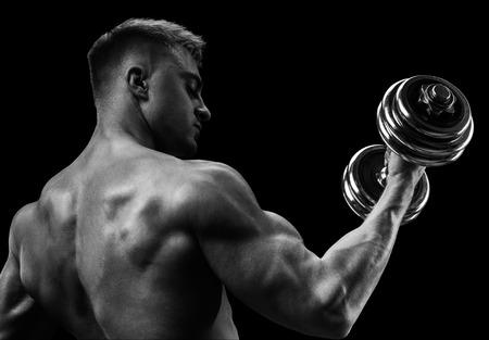Close-up van een knappe macht athletic man bodybuilder doet oefeningen met halters. Fitness gespierd lichaam op een donkere achtergrond.