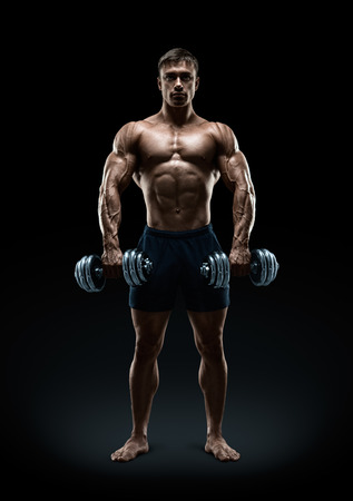 Handsome power athletic man bodybuilder doing exercises with dumbbell confidently looking forward. Fitness muscular body on dark background.