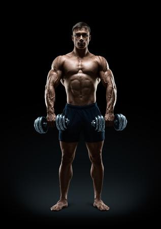 Knap macht atletische man bodybuilder doet oefeningen met halters met vertrouwen naar uit. Fitness gespierd lichaam op een donkere achtergrond.