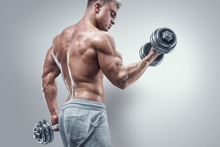 Handsome power athletic man in training pumping up muscles with dumbbell. Strong bodybuilder with six pack perfect abs shoulders biceps triceps and chest. Image with clipping path
