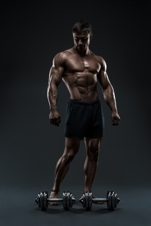 cuerpo hombre: Culturista muscular hermoso prepara para el entrenamiento de fitness. Estudio disparó sobre fondo negro.