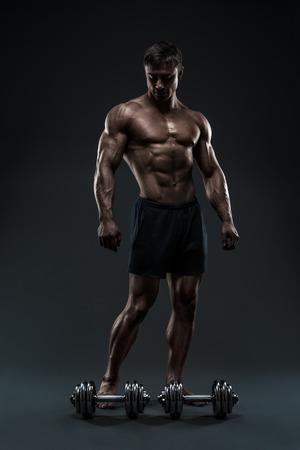 Knappe gespierde bodybuilder voorbereiding voor fitness training. Studio opname op zwarte achtergrond.