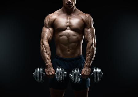 deportista: Poder guapo chico atlético culturista haciendo ejercicios con mancuernas. Musculoso cuerpo fitness en el fondo oscuro.