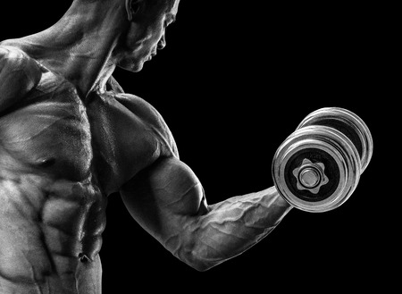 Handsome power athletic man in training pumping up muscles with dumbbell. Strong bodybuilder with six pack perfect abs shoulders biceps triceps and chest. Black and white image