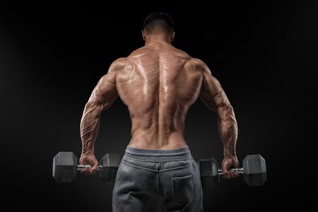 Gespierde mannelijke model bodybuilder doet oefeningen met halters keerde terug. Geïsoleerde over zwarte achtergrond.