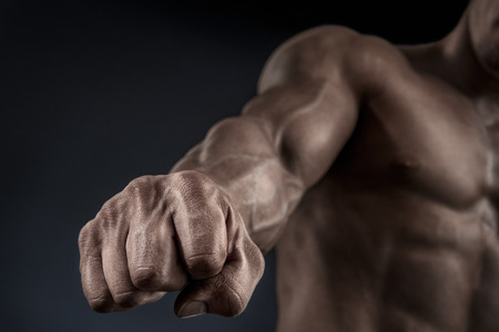 muscular build: Closeup of a man39s fist. Strong and power man39s hand with muscles and veins. Studio shooting. Stock Photo