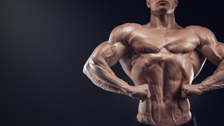 quadriceps: Handsome muscular bodybuilder posing on Front Lat Spread display lat width from the front chest thickness shoulder width front arm and forearm size quadriceps mass and separation and calf development from the front