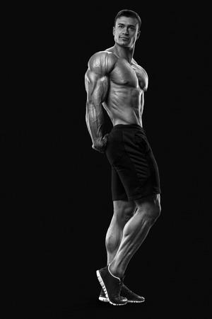 cuerpo hombre: Modelo masculino de la aptitud culturista muscular y en forma posando sobre fondo negro. Hombre joven fuerte y apuesto demostrar su torso musculoso y bíceps. Cuerpo de hombre musculoso con gran físico