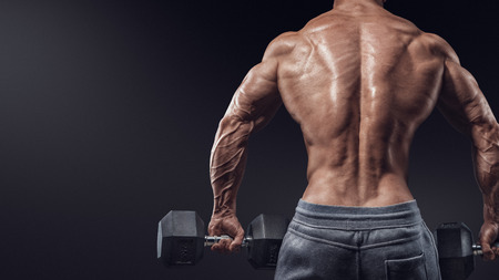 Muscular male model bodybuilder doing exercises with dumbbells turned back. Isolated over black background. Stock Photo