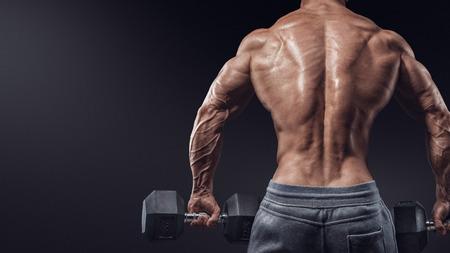cuerpo hombre: Muscular modelo masculino culturista haciendo ejercicios con pesas se volvi�. Aislado sobre fondo negro.