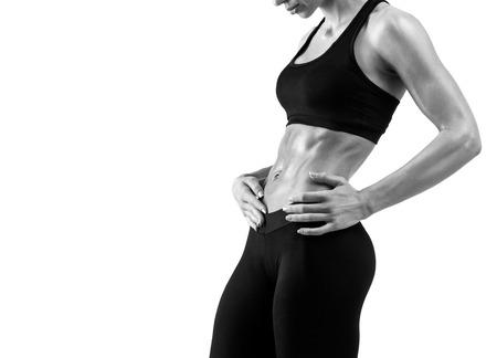 Fitness sportieve vrouw die haar goed getraind lichaam op een witte achtergrond. Sterke buikspieren tonen. Zwart-wit foto met copyspace voor tekst.