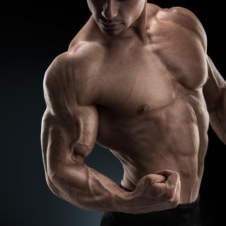 Knappe macht atletische man bodybuilder doet oefeningen met halters. Fitness gespierd lichaam op een donkere achtergrond.