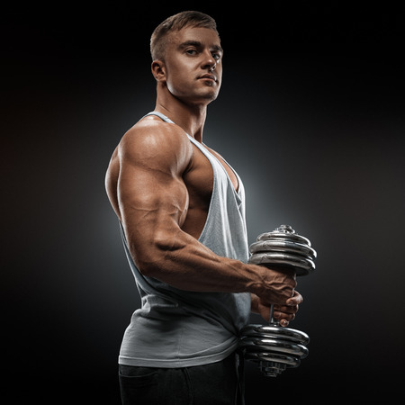 pectoral: Strong athlete in activewear ready to doing pumping up muscles with dumbbell confidently looking forward. Power bodybuilder with biceps triceps and chest