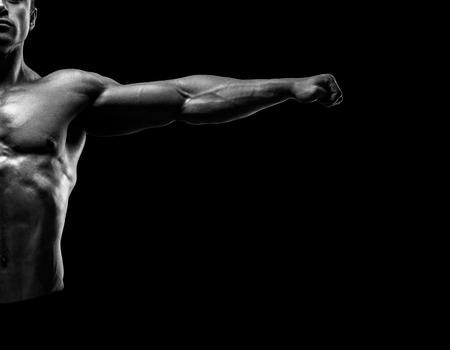fitness hombres: Handsome posando culturista muscular y mantener los brazos extendidos. Culturista joven muscular y aptos posando levantando las manos sobre fondo negro. Foto blanco y negro. Foto de archivo