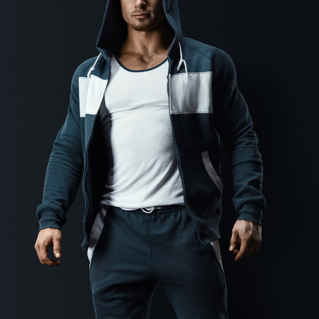 ropa deportiva: Modelo de fitness masculino atractivo con la camiseta abierta sobre fondo oscuro