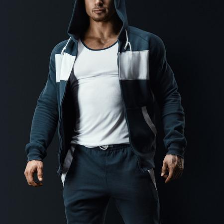 Sexy mannelijk fitness model met open sweatshirt op donkere achtergrond