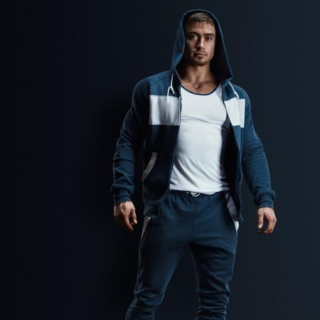 sudadera: Modelo de fitness masculino atractivo con la camiseta abierta sobre fondo oscuro