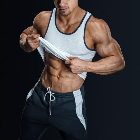 Modelo masculino atlético posando en ropa deportiva, tirando hacia arriba de la tapa del tanque de revelar abs muscular en forma. Aislado sobre fondo negro Foto de archivo - 43157322