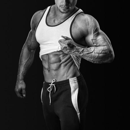 desnudo masculino: Culturista hermoso muestra su gran físico, hombros perfectos, bíceps, tríceps y tirando hacia arriba la parte superior del tanque para revelar abs muscular de ajuste. Aislado sobre fondo negro Foto de archivo