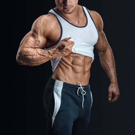 Handsome bodybuilder shows his great physique, perfect shoulders, biceps, triceps and pulling up tank top to reveal fit muscular abs. Isolated on black background