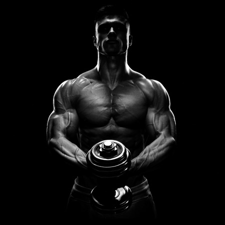 Silhouette of a bodybuilder. Power athletic man pumping up muscles with dumbbell. Confident young fitness man with strong core muscles, power hands and clenched fists. Dramatic light.