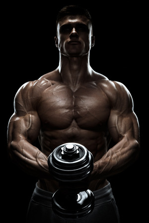 bodybuilding: Silhouette of a bodybuilder. Power athletic man pumping up muscles with dumbbell. Confident young fitness man with strong core muscles, power hands and clenched fists. Dramatic light.