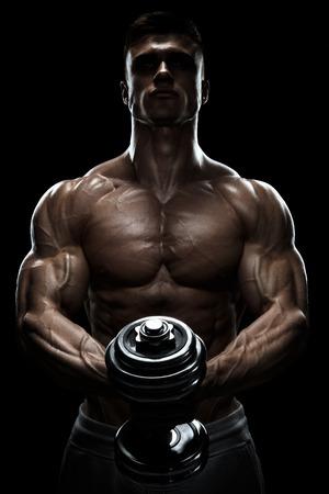 musculos: Silueta de un culturista. Poder hombre atlético bombeo de músculos con pesas. Hombre confidente joven de la aptitud con fuertes músculos de la base, fuentes de las manos y los puños apretados. Luz dramática.