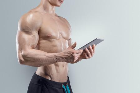 Close-up von sportlich und fit junge Mann mit einem digitalen Tablette