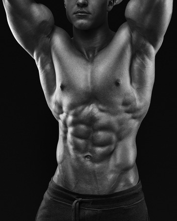 Sexy shirtless mannelijk model jonge bodybuilder stellen over zwarte achtergrond. Studio opname op zwarte achtergrond.